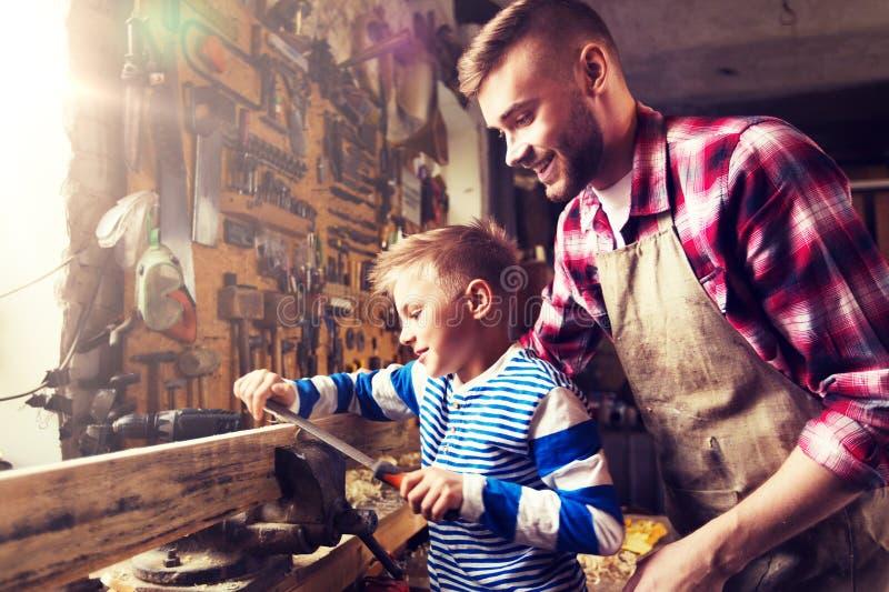 Отец и сын при терпуг работая на мастерской стоковое фото rf