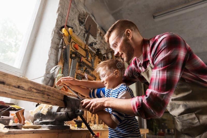 Отец и сын при терпуг работая на мастерской стоковое изображение