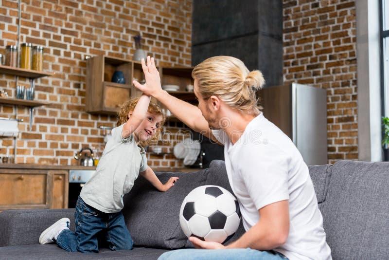 отец и сын при футбольный мяч давая максимум 5 пока сидящ совместно стоковые фотографии rf