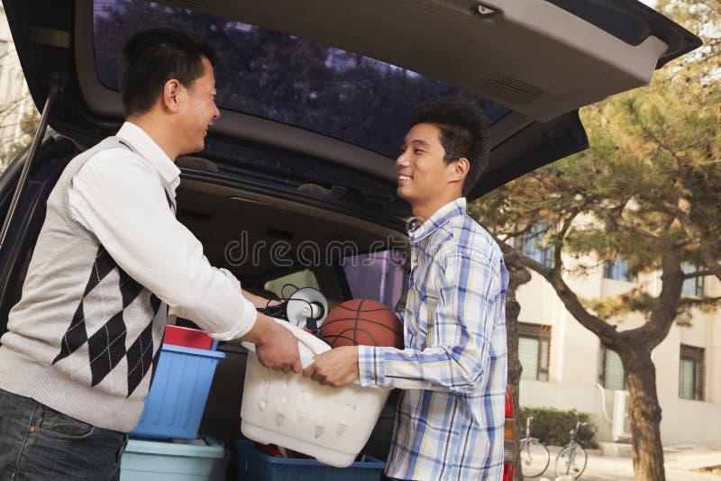 Отец и сын распаковывая автомобиль для коллежа стоковые фотографии rf