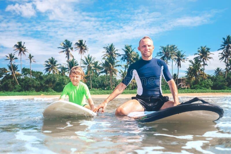 Отец и сын сидят на surfboards Первые занимаясь серфингом уроки стоковая фотография rf