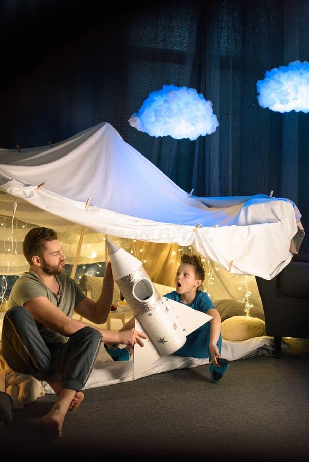 Отец и сын сидя совместно в форте одеяла и играя с ракетой игрушки стоковые фото