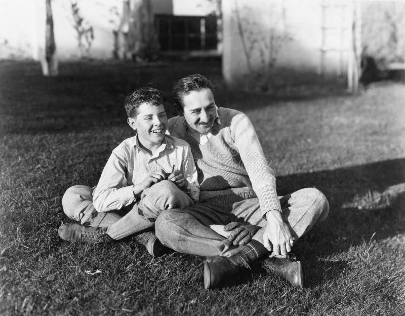 Отец и сын сидя совместно на траве в заднем дворе (все показанные люди более длинные живущие и никакое имущество не существует S стоковые фотографии rf