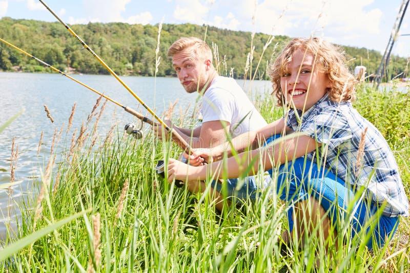 Отец и сын удят совместно на озере стоковые изображения
