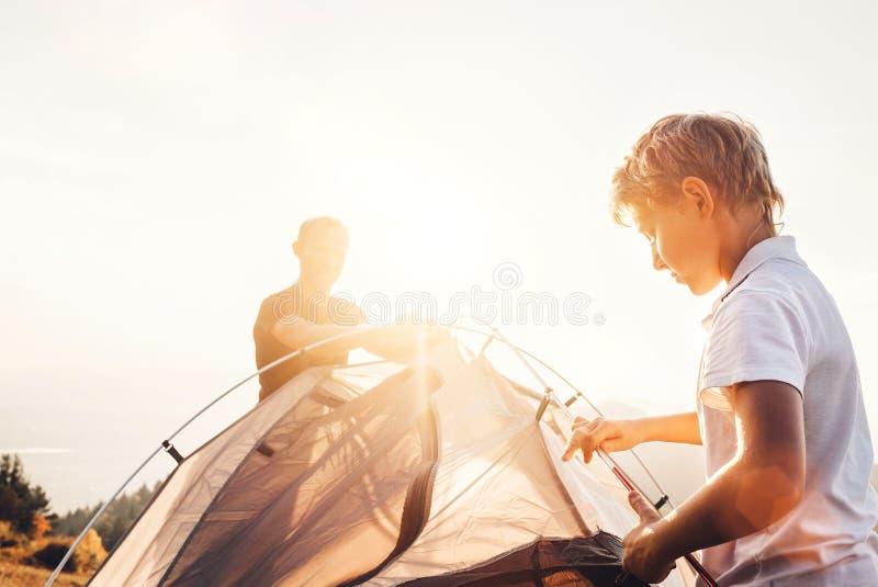 Отец и сын устанавливают touristic шатер для располагаться лагерем стоковые фото