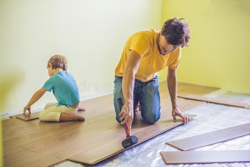 Отец и сын устанавливая новый деревянный слоистый настил ультракрасно стоковые фото