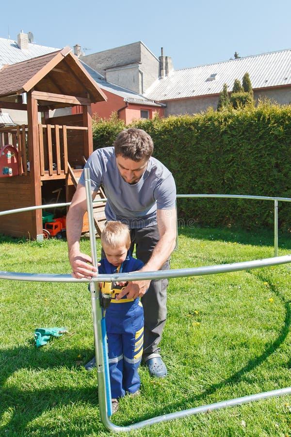 Отец и сын устанавливая большие батуты сада стоковое изображение rf