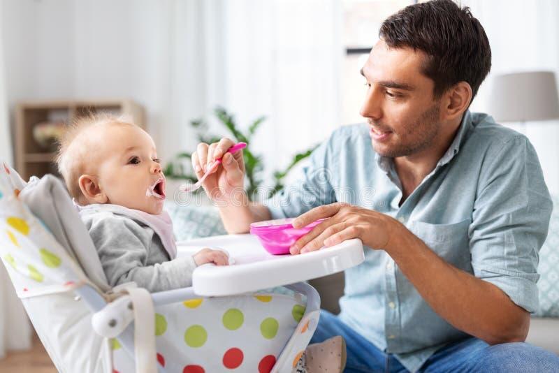 Отец кормить счастливый младенца в высоком стульчике дома стоковая фотография rf