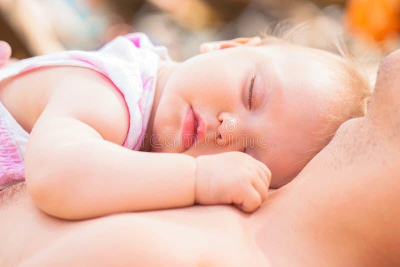 отец младенца Младенец лежа на его комоде ` s отца стоковые фотографии rf