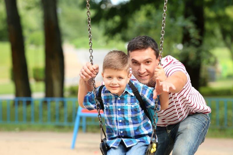 Отец нажимая его сына на качаниях outdoors стоковое фото