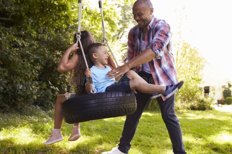 Отец нажимая детей на качании автошины в саде стоковые фотографии rf