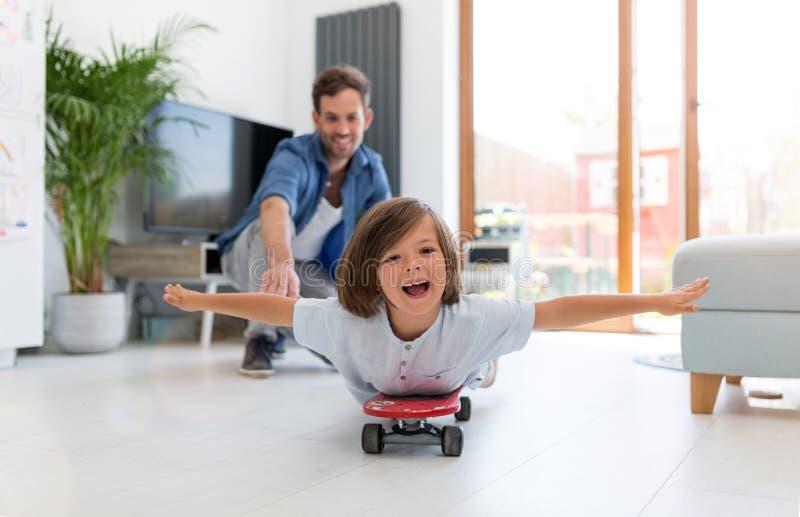 Отец нажимая сына кладя на скейтборд стоковые изображения