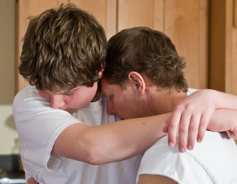 отец обнимая сынка предназначенного для подростков стоковое изображение