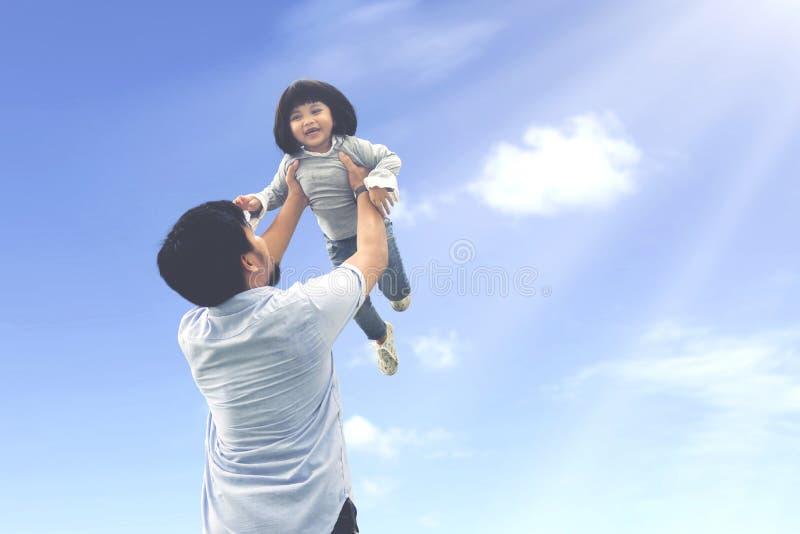 Отец поднимает его дочь под ясное небо стоковое изображение