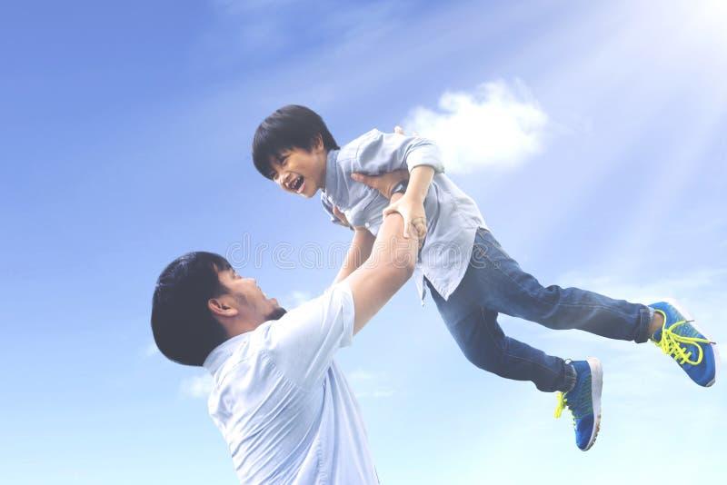 Отец поднимает его сына с счастливым выражением стоковое изображение rf