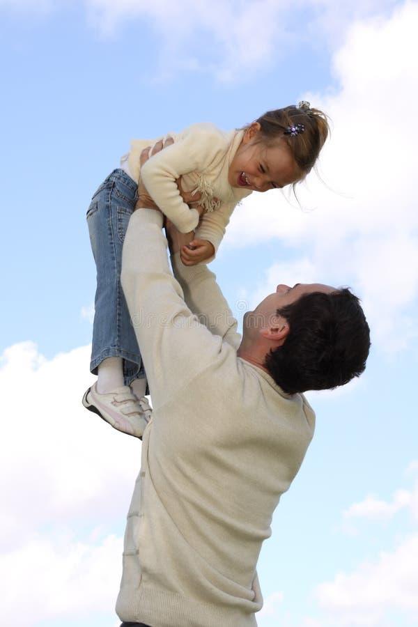 Отец поднимая маленькую дочь стоковые фото