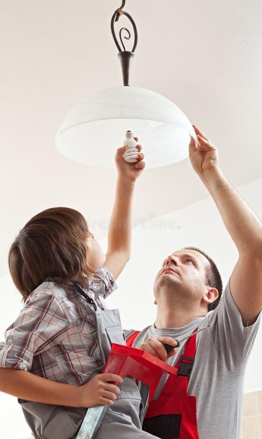 Отец порции мальчика устанавливая потолочную лампу - привинчивающ в lig стоковое фото