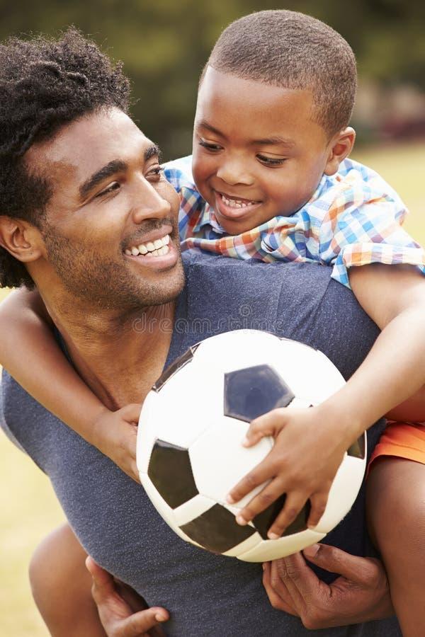 Отец при сын играя футбол в парке совместно стоковая фотография rf