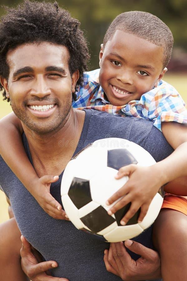 Отец при сын играя футбол в парке совместно стоковые фотографии rf