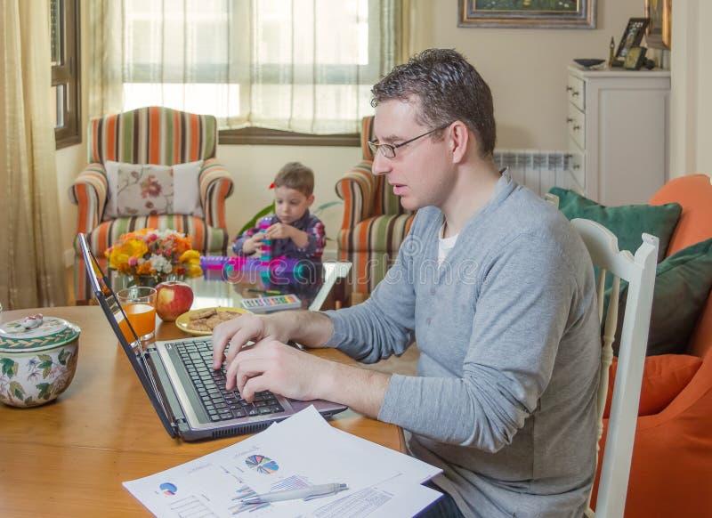 Отец работая в играть домашнего офиса и сына стоковые фото