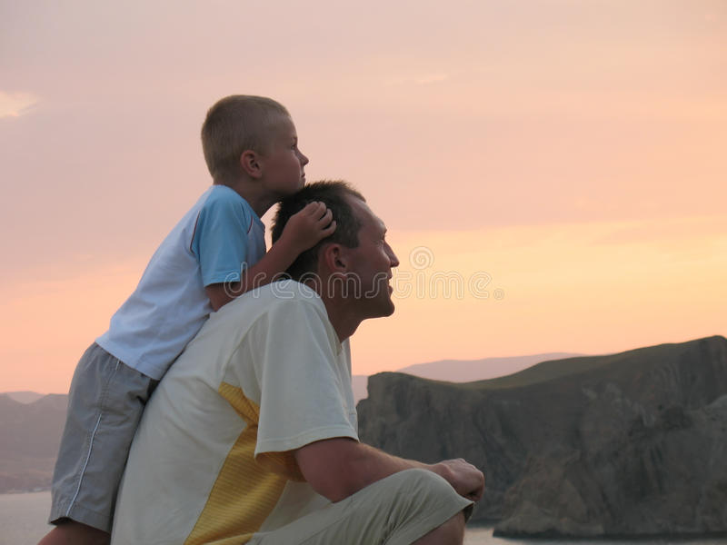 отец ребенка смотря заход солнца стоковые изображения rf
