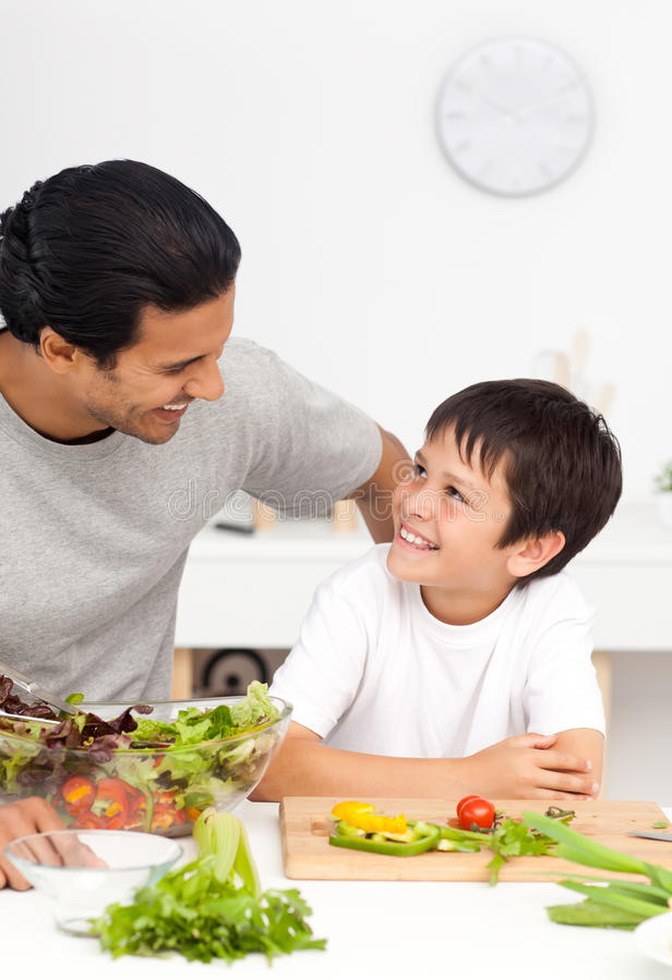 отец счастливый помогающ его сынку кухни стоковые изображения rf