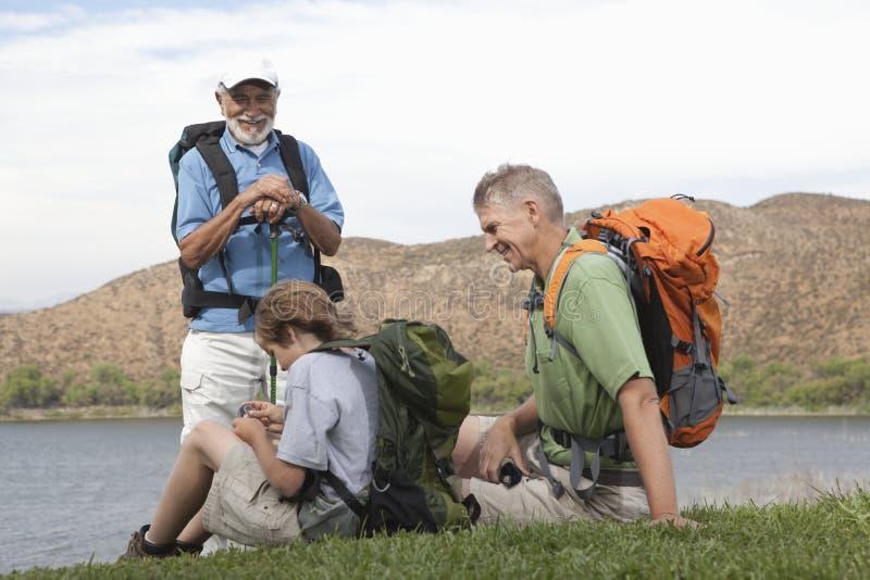 Отец, сын и внук сидят озером стоковое изображение rf