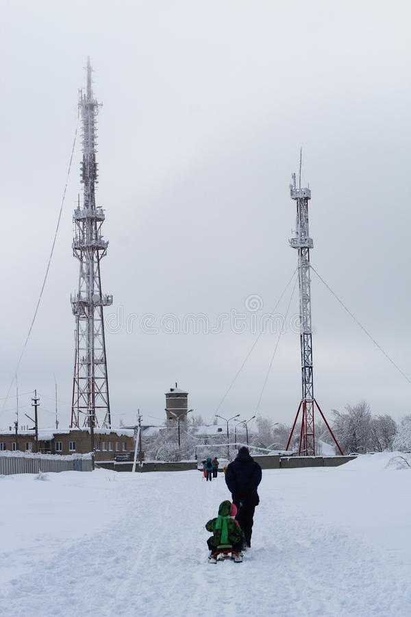 Отец с детьми на скелетоне идет к башне ТВ и башне клетки в тумане туманная зима утра стоковое фото
