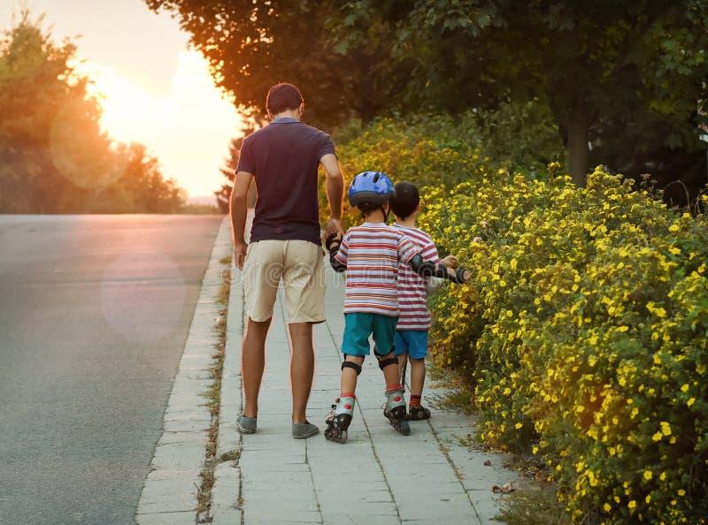 Отец с детьми на прогулке вечера стоковое изображение rf