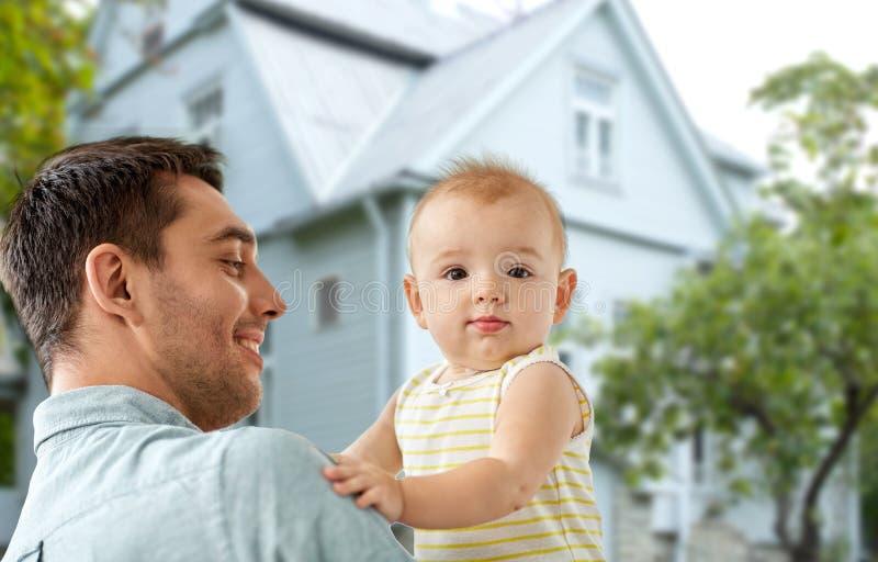 Отец с маленькой дочерью младенца над домом стоковое фото