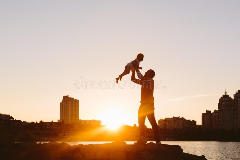 Отец с маленьким ребенком на заходе солнца стоковое изображение rf