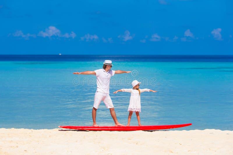 Отец с маленькой дочерью на практиковать пляжа стоковая фотография rf
