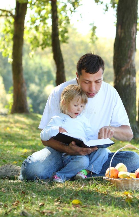 Отец с молодой дочью прочитал библию в природе стоковые изображения rf