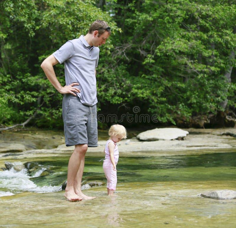 Отец с младенцем идет в реку стоковая фотография