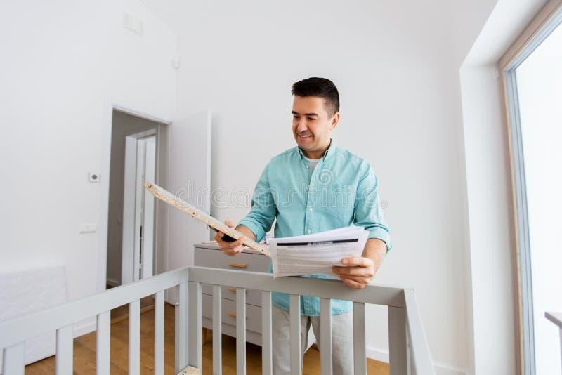 Отец с ручной собирая кроватью младенца дома стоковые изображения