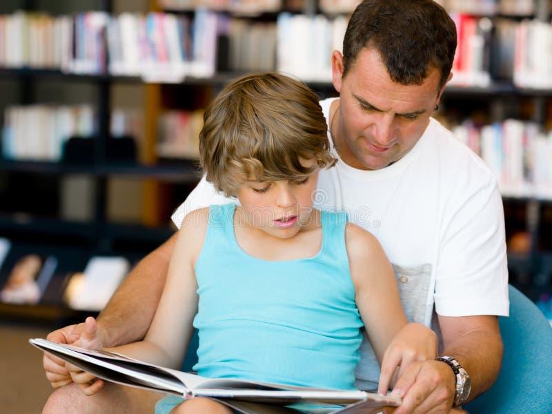 Отец с сыном в библиотеке стоковая фотография