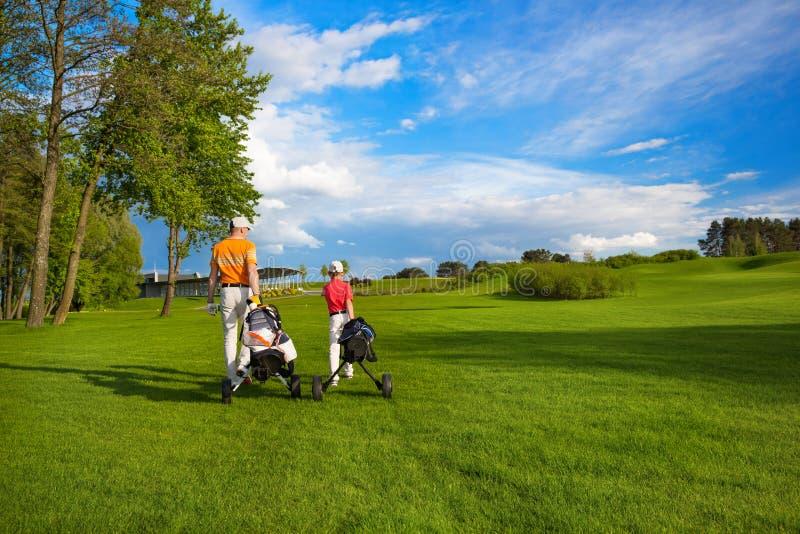 Отец с сыном на поле гольфа стоковое фото