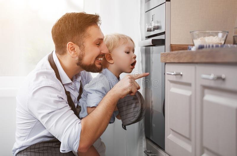 Отец с сыном ребенка подготавливает еду, печет печенья стоковое изображение rf