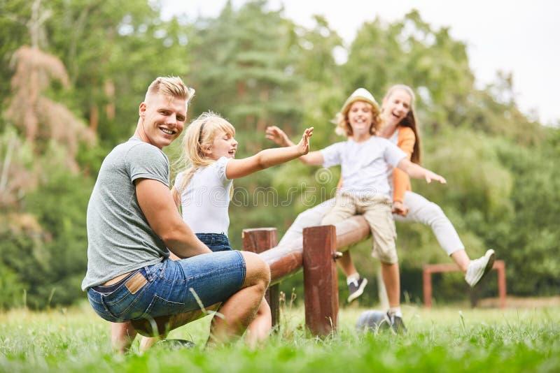 Отец трясет с детьми на спортивной площадке стоковое изображение rf