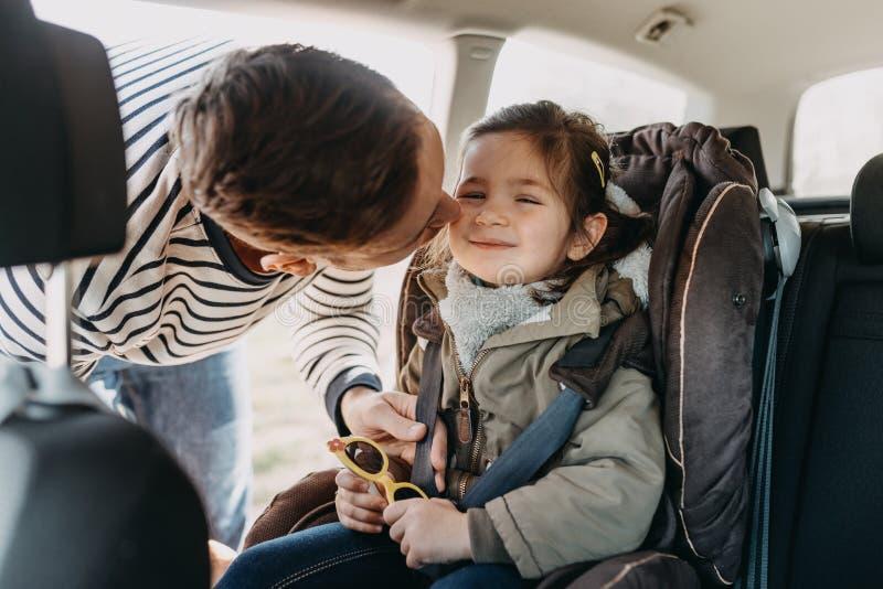 Отец целует его дочь малыша buckled в ее место малолитражного автомобиля стоковое фото rf