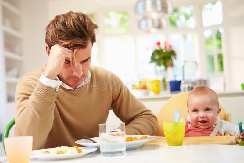 Отец чувствуя отжатый на времени принятия пищи младенца стоковые фото