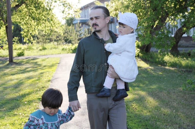 Отец Thinkful идя в парк с 2 дочерьми на солнечном дне папа с 2 маленькими ребеятами в парке внешнем стоковые изображения rf