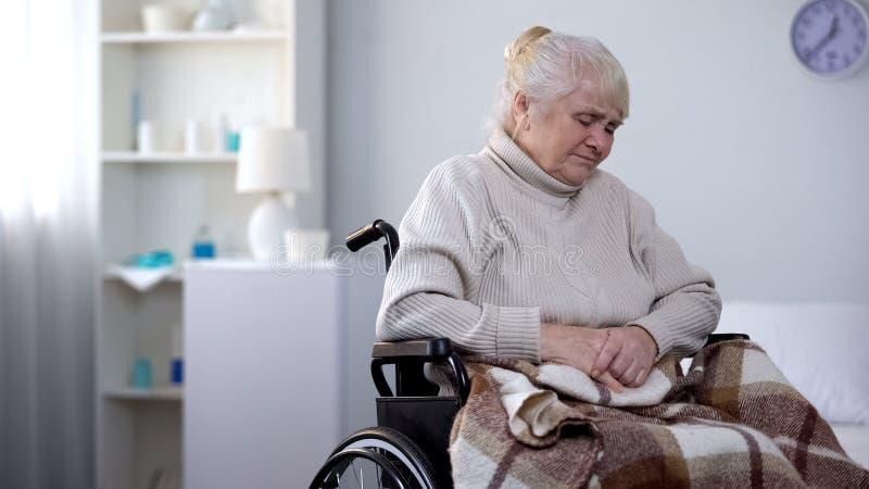 Отжатая кресло-коляска женщины покрыла одеяло, отсутствующую семью, тоскливость старости стоковые изображения rf