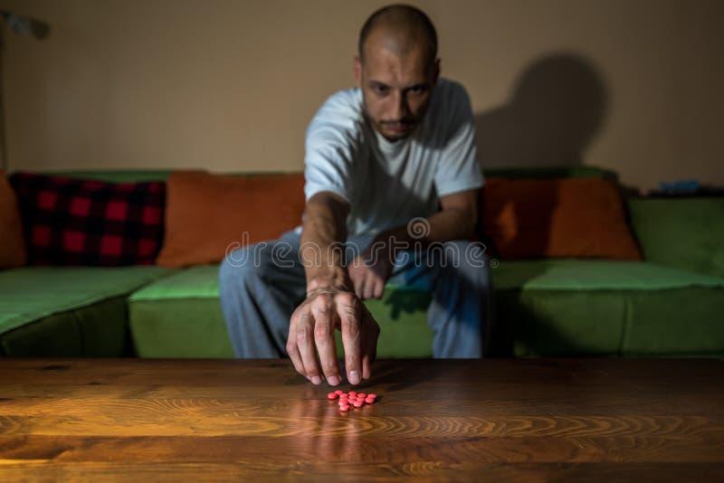 Отжатое страдание человека от суицидальной депрессии хочет покончить жизнь самоубийством путем принимать сильные лекарства и табл стоковые фото