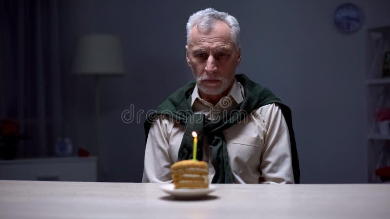 Отжатый старший человек смотря именниный пирог, празднуя праздник самостоятельно дома стоковое фото rf