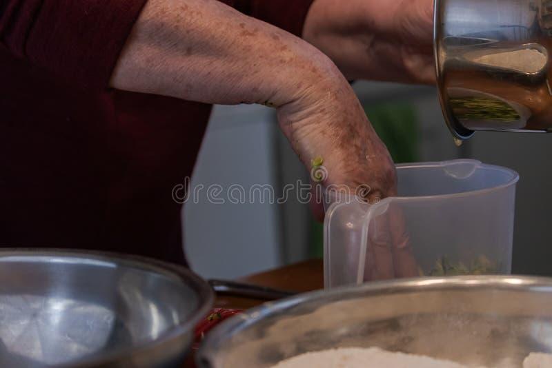 Отжимать shredded цукини в ясную пластиковую измеряя чашку стоковое фото rf