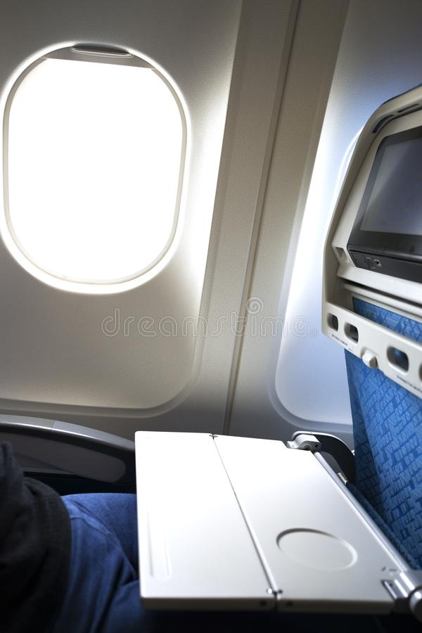 Откидной столик самолета раскрытый на спинке сидения окном стоковое фото rf