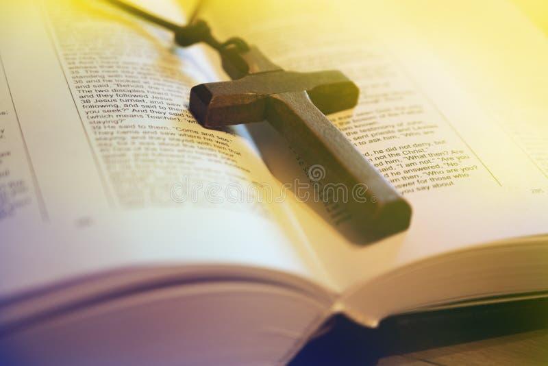 Открытая библия и деревянный крест стоковые изображения