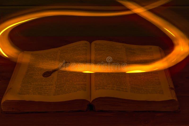 Открытая библия на таблице стародедовский ключ Огонь летая над библией освещает свои страницы стоковая фотография