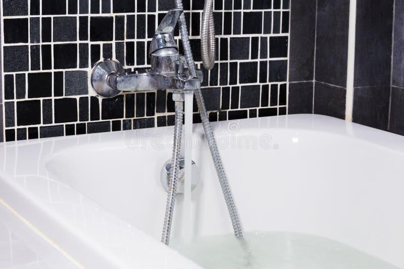 Открытая вода от faucet к ванне в ванной комнате стоковые фото